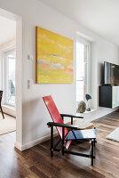 Klassischer Designerstuhl unter gelbem Gemälde