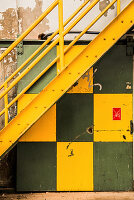 Yellow steel staircase above green and yellow sliding door in factory