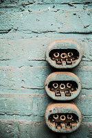 Three dusty old plug sockets on pale blue wall