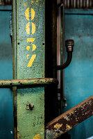 Gelbe Zahlen auf einem Stahlträger mit abgeblätterter Farbe
