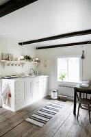 Weiße Küchenzeile in einer ländlichen Wohnküche mit Holzboden