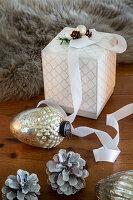 Geschenkschachtel, Weihnachtsbaumanhänger und Zapfen auf Holztisch