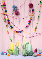 Colourful garlands of pompoms and ceramic cactus-shaped candlesticks