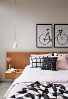 Doppelbett mit Betthaupt und integriertem Nachttisch, darüber zweiteiliges Bild mit Fahrradmotiv