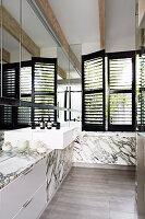 Waschbecken in elegantem Badezimmer mit Marmorverkleidung