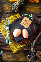 A rustic Easter table setting with knotty branches and fresh eggs