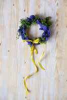 Small wreath of grape hyacinth flowers with yellow ribbon on wooden surface
