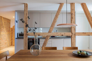 Dining area and simple fitted kitchen separated by wooden beams