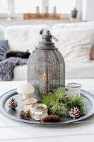 Vintage lantern, tealights and conifer sprigs on tray