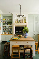 Soft green coloured kitchen with wooden stools and collection of plates stacked on open shelves
