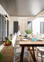 Gedeckter Holztisch auf sonniger, überdachter Terrasse