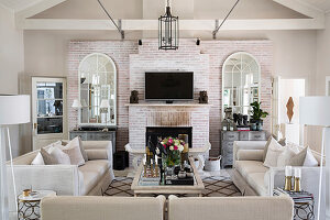 Helle Sofagarnitur und Couchtisch im Wohnzimmer mit Kamin