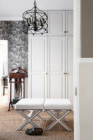 Valet stand next to white wardrobe and upholstered stools in dressing room