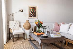 Couchtisch aus Holz, Polstersessel und Sofa im Wohnzimmer