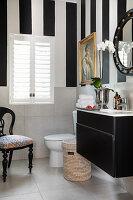 Waschtisch, Toilette und Polsterstuhl in schwarz-weißem Badezimmer