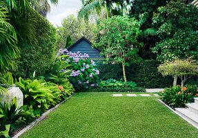 Große Rasenfläche und Randbepflanzung in gepflegtem Garten