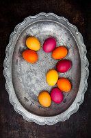 Easter eggs coloured with organic dyes on a pewter plate