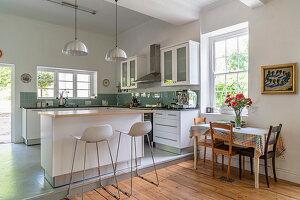 Weiße Küche mit Betonboden und grünen Spritzschutzfliesen, im Vordergrund Tisch mit Stühlen auf Holzdielenboden