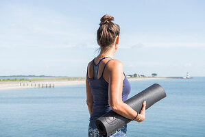 Woman holding yoga mat next to the sea