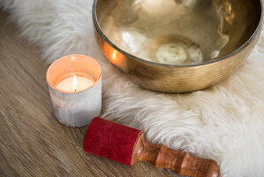 Singing bowl and tealight on fur rug