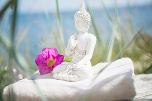 Buddha figurine and flower on towel
