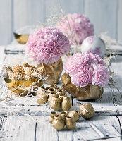 Rosa blühende Nelken in goldfarbenen Schalen