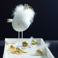 Chicken ornament, golden effs and feathers on white tray