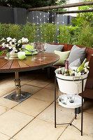 Getränkekühler neben dem runden Gartentisch auf der Terrasse