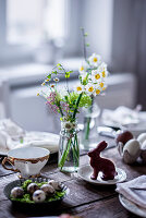 Easter table with spring flowers, quail eggs and chocolate bunny