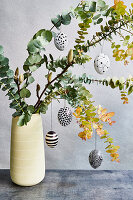 Easter eggs decorated with geometric patterns hanging on twigs