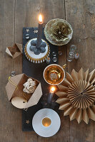Festive arrangement of gilt china, paper flowers, star and grey candles on slate board decorating table