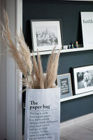 Dry grasses in paper bag in front of narrow shelves