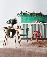 Runder Tisch mit Stühlen und grüne Fliesen über Unterschrank in weihnachtlich dekorierter Küche