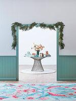 Durchgang mit Weihnachtsgirlande, im Hintergrund runder Tisch mit Blumenstrauß und Geschenken