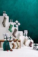 Weiße Treppe mit Weihnachtsgeschenken und Nikolausstrümpfen dekoriert vor grüner Wand