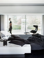 Designer furniture in minimalist, monochrome bedroom; person walking past windows