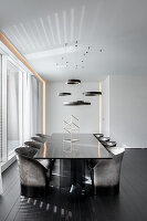 Elegant, black dining table with designer chairs in minimalist interior