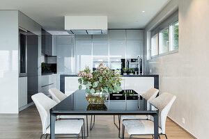 Modern dining table in minimalist kitchen-dining room in grey and beige