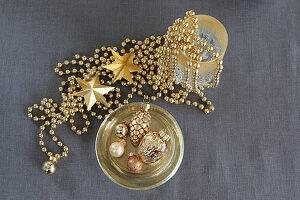 Weihnachtsschmuck in Gold auf grauem Leinenstoff
