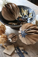 Original arrangement of honeycomb balls handcrafted from brown paper on rustic wooden table