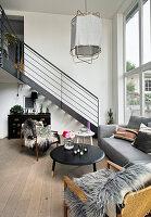 Wohnraum mit hohen Wänden, Sitzecke in Grau und Treppe zur Galerie