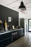 Küchenzeile mit schwarzen Schrankfronten und schwarzer Rückwand