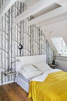 Bett unter Dachschräge vor Wand mit Waldmotiv-Tapete