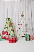 Suspended DIY Christmas tree made from rope and branches, wrapped presents and step ladder