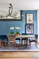 Magnolia light fitting above dining table with orchids and artworks on blue wall