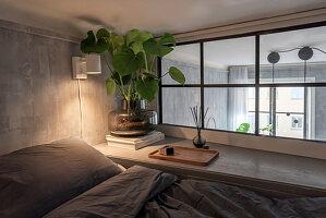 Monstera am Innenfenster neben dem Bett im Schlafzimmer in Grau