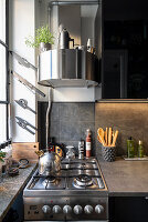Round extractor hood above gas cooker in small grey kitchen