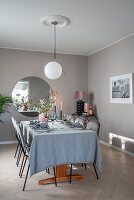 Set table in dining room in shades of grey with pink accents