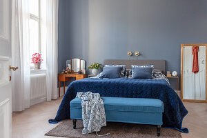 Blue velvet throw on bed and bedroom bench in bedroom of period apartment