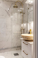 Marble countertop sink, glass shower screen and brass shower fittings in elegant bathroom